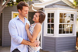 Portrait Of Excited Couple Standing Outside New Home