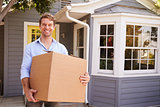 Man Carrying Box Into New Home On Moving Day