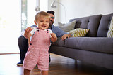 Father Watching Baby Daughter Take First Steps At Home