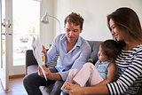 Parents Reading With Baby Daughter On Sofa At Home
