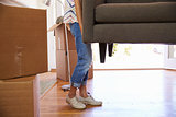 Close Up Of Woman Carrying Sofa Into New Home On Moving Day