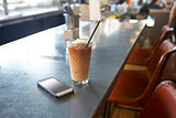 Mobile Phone And Cold Press Coffee On Cafe Counter