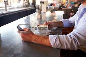 Close Up Of Man Checking Messages On Phone In Coffee Shop