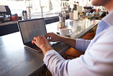 Close Up Of Man Using Laptop In Coffee Shop