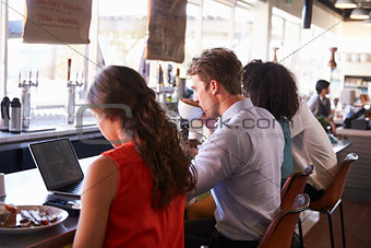 Business People Working At Counter In Coffee Shop