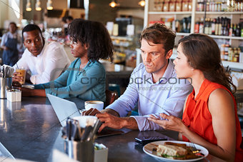 Group Enjoying Business Lunch At Delicatessen Counter