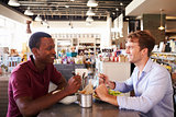 Two Men Enjoying Lunch In Delicatessen Restaurant