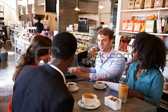 Business Group Having Informal Meeting In Cafe
