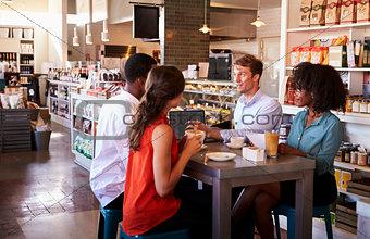 Business Group Having Informal Meeting In Cafe