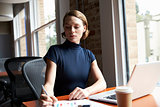 Businesswoman Working On Laptop And Making Notes On Document