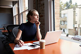 Thoughtful Businesswoman Working On Laptop By Window