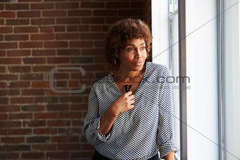 Thoughtful Mature Businesswoman Looking Out Of Office Window