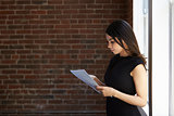 Businesswoman Reading Document Standing By Office Window