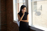 Businesswoman Making Phone Call Standing By Office Window