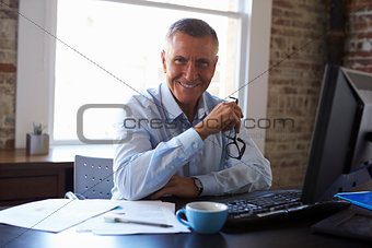 Portrait Of Mature Businessman Working In Office