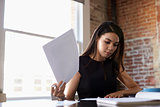 Businesswoman Making Notes On Document In Office