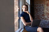 Businesswoman Sitting By Window Working On Laptop