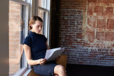 Businesswoman Sitting By Window Reading Documents