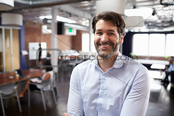 Portrait Of Businessman In Modern Open Plan Office
