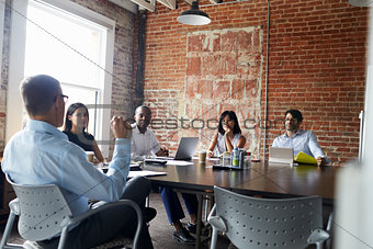 Group Of Businesspeople Meeting In Modern Boardroom