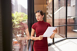 Businesswoman holding document, looking out of office window