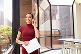 Smiling young white businesswoman on phone in modern office