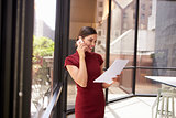 Smiling white woman on phone in office looking at document