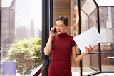 Young white businesswoman on phone looking out office window