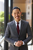 Young Asian businessman smiling to camera, vertical