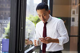 Asian businessman using phone in modern office, close up