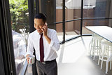 Happy Asian businessman on the phone in modern office