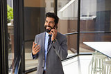Smiling middle aged Hispanic businessman on phone in office