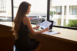Businesswoman sitting in modern office reading a document