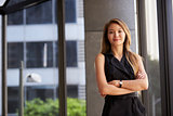Young Asian businesswoman looking to camera, arms crossed