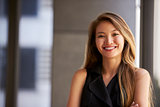 Young Asian businesswoman smiling to camera, close up