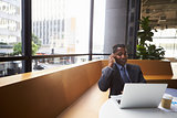 Middle aged black businessman using phone in a modern office