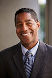 Middle aged black businessman smiling to camera, vertical