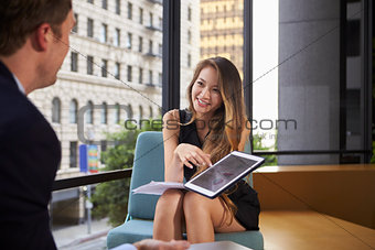 Businessman and woman showing tablet at an office meeting