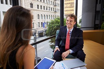 Businessman and woman using tablet at an office meeting