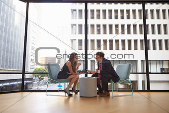 Businessman and woman meeting in modern office, full length