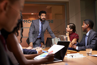 Businessman addressing team at a boardroom meeting, close up