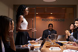 Black businesswoman addressing team at meeting, low angle