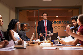 Smiling businessman addressing team at meeting, low angle