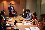 Businessman stands gesturing to colleagues at a meeting