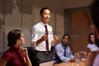 Asian businessman standing to address colleagues at meeting