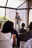 Hispanic man presents business seminar to audience, vertical