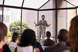 Hispanic man gesturing to audience at business seminar
