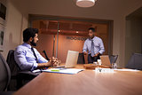 Businessman stands talking to work colleague late in office
