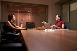 Two businesswomen working late in an office talking