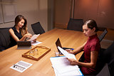 Two businesswomen doing paperwork late in an office